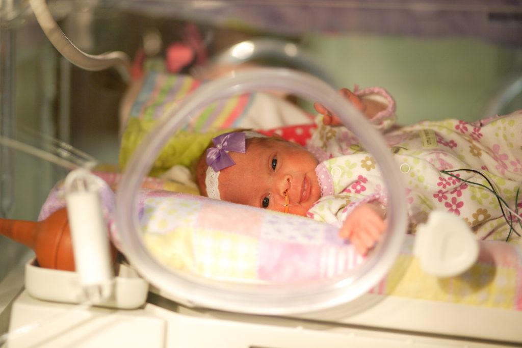 baby girl in a neonatal isolette