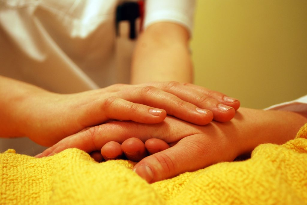 medical person holding the hand of a patient on a yellow blanket